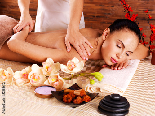 Masseur doing massage on woman body in spa salon