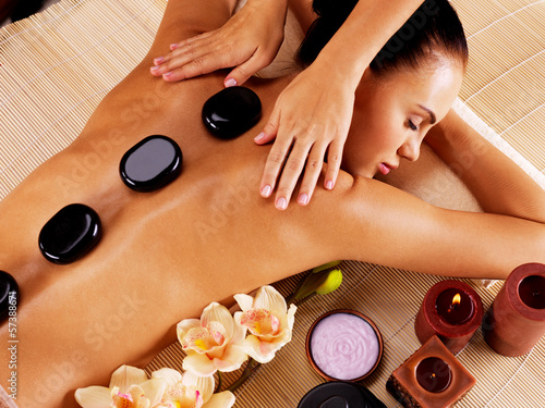 Leinwanddruck Bild Adult woman having hot stone massage in spa salon