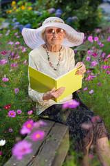 Elegant elderly lady reading in the garden.