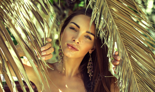 Beautiful woman between palm leaves - 57391880