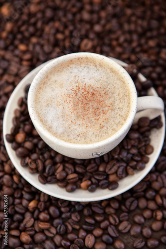 Cup of cappuccino  with coffee beans around