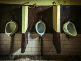 Three dirty urinals in public gents