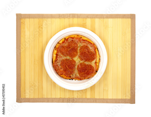 A plate of pepperoni pizza on a wood place mat