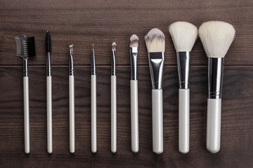 white make-up brushes on wooden table
