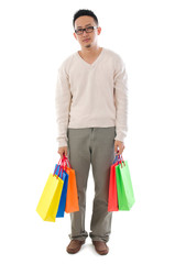 Bored Asian man holding shopping bags