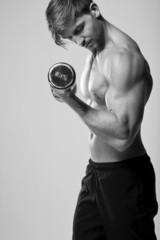 junger Mann beim Krafttraining und Muskelaufbau mit Hantel
