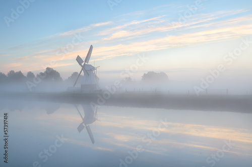Dutch windmill in dense fog during sunrise