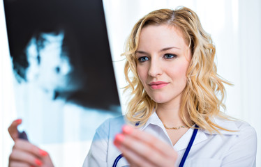 Smiling female doctor looking at X-rays in her office