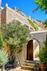 greece monemvasia view of stone houses with colorful flowers amo
