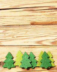 Tannenbäume aus Filz vor Holzhintergrund