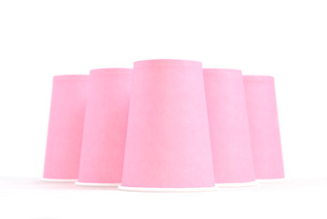 pink recycling paper glasses and one blue standing out on white