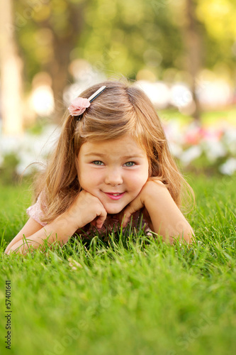 Happy beautiful little girl lying on the grass
