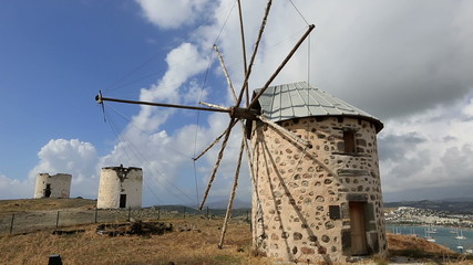 old windmill with white clouds and blue sky