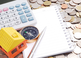 House model and compass with notebook on coins background