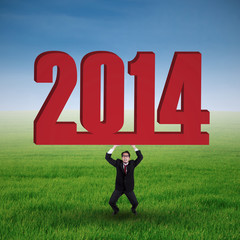 Asian businessman lifting a New year 2014