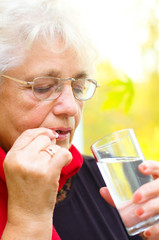 senior woman holding a pill in her hand