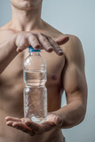 Muscular male model showing bottles of water
