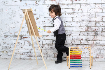 Little boy in bow tie stands next to easel and colorful abacus