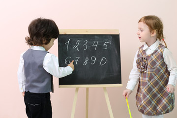 Little boy shows by finger figures at chalkboard for cute girl