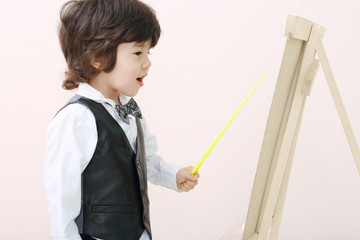 Little brunet boy with yellow pointer stands near wooden easel