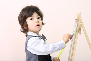 Little boy with yellow pointer draws with chalk on chalkboard