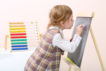 Little girl draws with chalk on chalkboard near colorful abacus