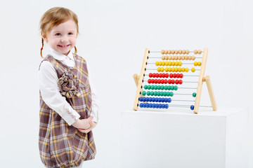 Little happy girl stands near colorful abacus on big white cube