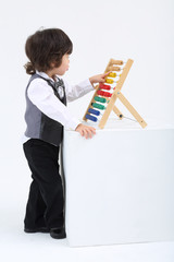 Little boy play with colorful abacus on big white cube in studio