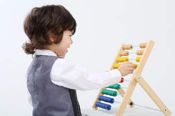 Little happy boy in vest plays with colorful abacus