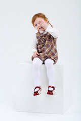 Little cute girl sits on big white cube