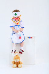 Little girl dressed as nurse bandages head to toy rabbit