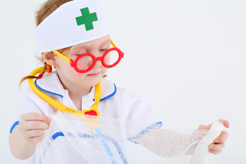 Little girl dressed as nurse spreads bandage on white