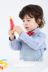 Little boy holds toy medical thermometer on white