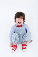 Little boy inl jumpsuit sits on floor and cries
