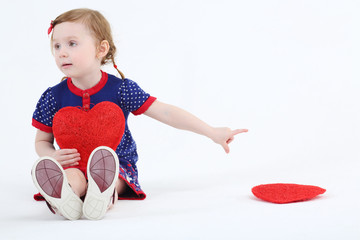 Little girl sits with red heart and reaches out