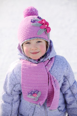 Little girl in pink scarf and hat smiles and looks at camera