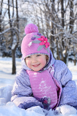 Happy little girl in pink scarf and hat lies in snow and looks