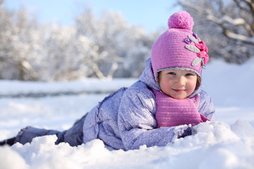 Warmly dressed little happy girl in pink scarf and hat lies