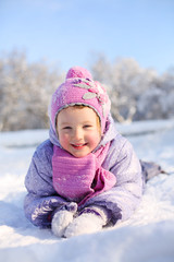 Little girl in pink scarf and hat lies on stomach on snow