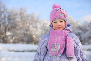 Little smiling girl in pink scarf and hat stands near trees