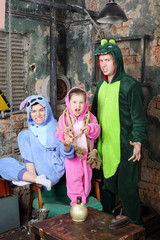 Father, mother and little daughter in costumes of dragons
