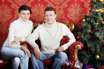 Husband and wife in white sweaters and jeans near Christmas tree