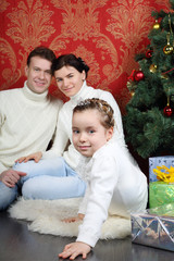 Family sit on floor with gifts near Christmas tree at home