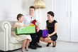 Father and mother give gifts to little daughter at sofa
