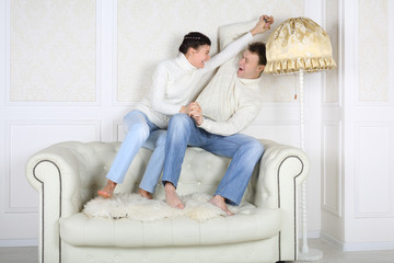 Smiling husband and wife sits on back of white sofa