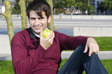 junger mann im park mit apfel