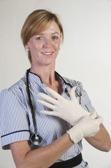Nurse pulling on surgical gloves