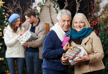 Senior Couple Holding Christmas Presents With Children In Store
