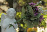 little cemetery angel figure holding a huge bouquet of flowers