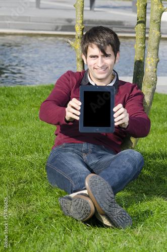 junger mann zeigt tabletpc